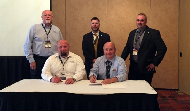 Derco Vice President Mark Konzal (center) and Technical Solutions Manager Rich Latus (right) join Chief Systems Engineer Kaan Tuncel (seated right) in signing the distribution agreement with Arkwin Business Unit Manager Bernard Kierez (seated left) and Sales Engineer Peter Muenzen (left).